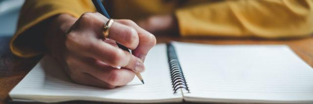 Zoomed in picture of a woman with a yellow long sleeve shirt adn a ring on her pointer finger writing in a notebook with a pencil