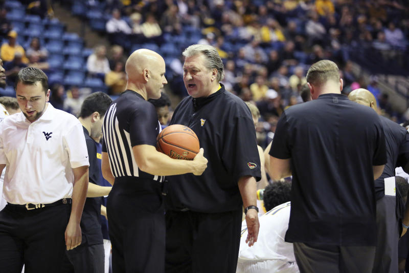 West Virginia's Coach Bob Huggins discusses a call with a referee during the second half of an NCAA college basketball game Monday Nov. 18, 2019, Morgantown, W.Va. (AP Photo/Kathleen Batten)