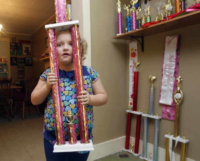 "In this photo taken Monday, Sept. 10, 2012, seven-year-old beauty pageant regular and reality show star Alana ""Honey Boo Boo"" Thompson shows one of her many trophies in her home in McIntyre, Ga. The reality show ""Here Comes Honey Boo Boo"" centers around Alana, her mother June Shannon and their family. (AP Photo/John Bazemore)"