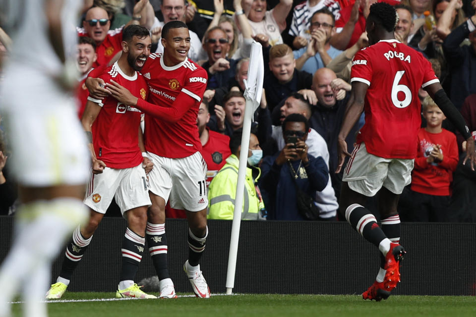 Manchester United's Portuguese midfielder Bruno Fernandes (left) celebrates scoring his team's first goal against Leeds with Mason Greenwood (centre) and Paul Pogba.
