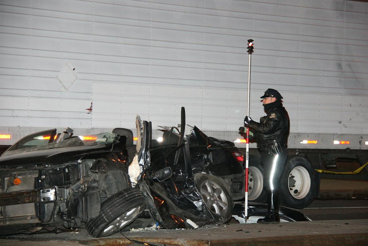 In this photo provided by VosIzNeias.com, a police officer works at the scene of a car accident that took the lives of an expectant couple in Brooklyn's Williamsburg neighborhood, Sunday, March 3, 2013, in New York. The young couple who had taken a car service to a hospital for the birth of their first child were killed en route by the driver of a BMW who fled the scene, but the couple's baby boy survived, born prematurely, authorities and a neighbor said. Their infant son was in serious condition at a hospital, and the driver of car that was hit was in stable condition. (AP Photo/VosIzNeias.com, Shimon Gifter)