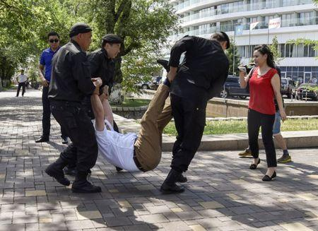 Police officers detain an opposition supporter attempting to stage a protest rally in Almaty, Kazakhstan June 23, 2018.  REUTERS/Mariya Gordeyeva