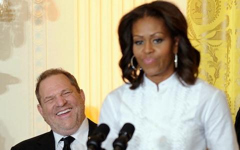 Movie mogul Harvey Weinstein, left, smiles as first lady Michelle Obama speaks in the East Room of the White House  - Credit: AP