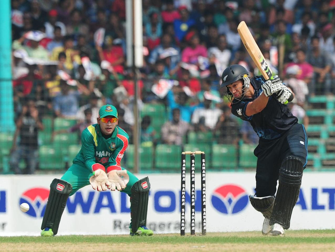 New Zealand batsman Ross Taylor (R) plays a shot as Bangladesh captain Mushfiqur Rahim looks on during the third One-Day International (ODI) cricket match between Bangladesh and New Zealand at Khan Jahan Ali Stadium in Fatullah, on the outskirts of Dhaka on November 3, 2013.  AFP PHOTO/ Munir uz ZAMAN        (Photo credit should read MUNIR UZ ZAMAN/AFP/Getty Images)