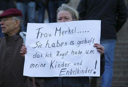 A woman holds up a placard reading 'Mrs Merkel you have achiedved that i'm afraid of the furture for my children and grandchildren' prior to a demonstration by anti-immigration right-wing movement PEGIDA (Patriotic Europeans Against the Islamisation of the West) in Cologne, Germany, January 9, 2016. REUTERS/Wolfgang Rattay