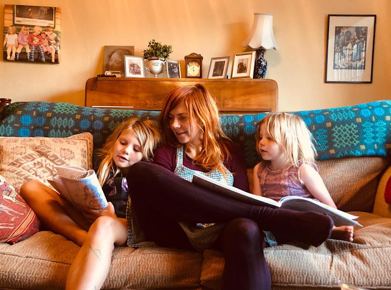 Mum sitting reading with her two daughters