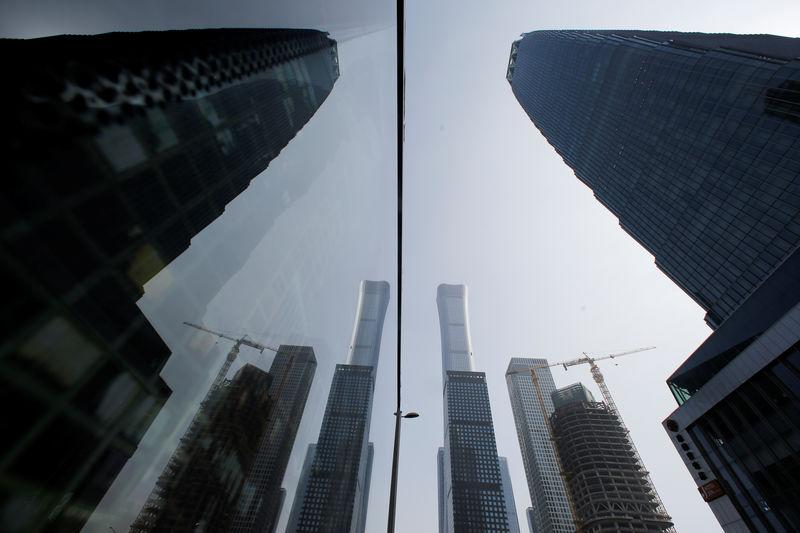 Skyscrapers in the Central Business District (CBD) are reflected in a window one day before the opening session of the National People's Congress (NPC) in Beijing