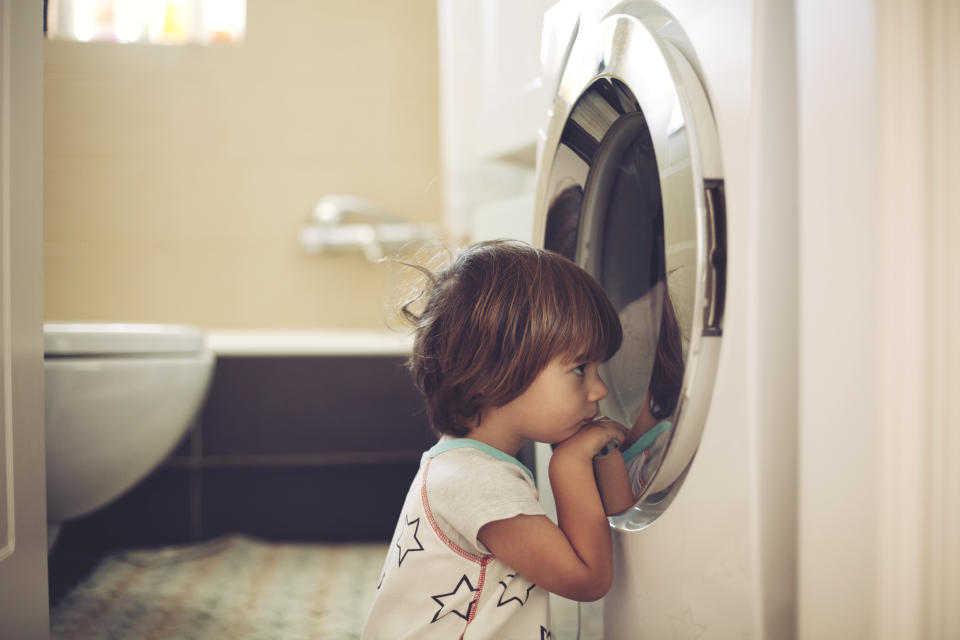 Washing machines are releasing millions of plastic microfibres into the ocean. Pictured is a stock image of a child looking into a front-loading washing machine.
