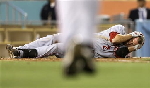 Cincinnati Reds' Zack Cozart rolls on the ground after getting hit by a pitch during the fifth inning of a baseball game against the Los Angeles Dodgers in Los Angeles, Monday, July 2, 2012. (AP Photo/Chris Carlson)