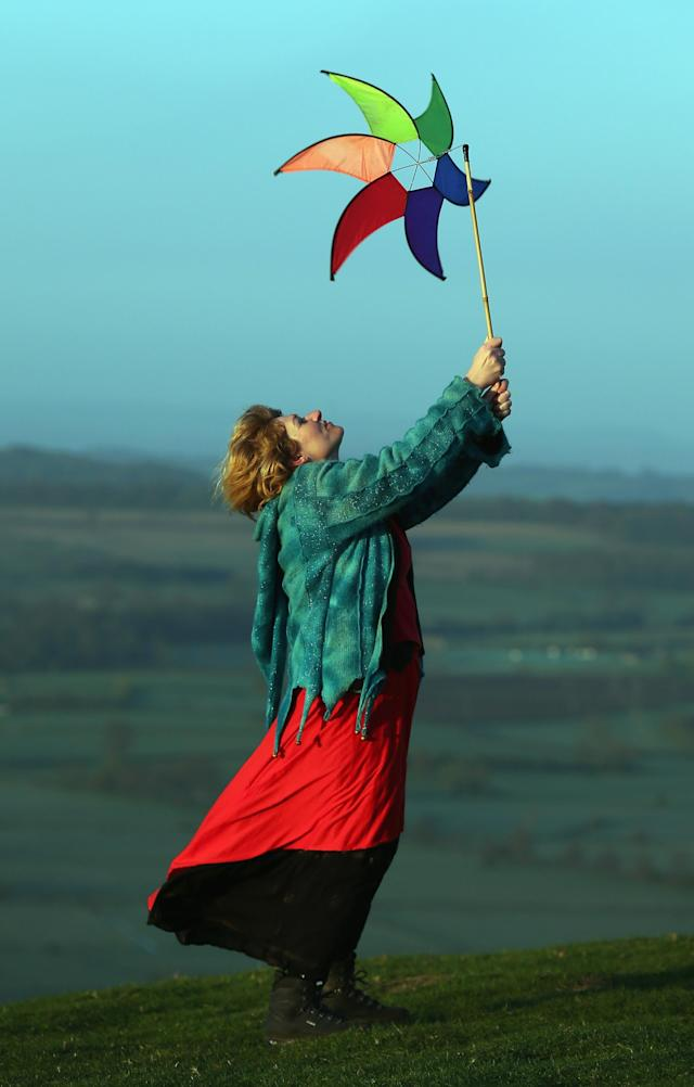 GLASTONBURY, ENGLAND - MAY 01: A woman holds a windmill as she watches the sun rise as they join in a Beltane dawn celebration service in front of St. Michael's Tower on Glastonbury Tor on May 1, 2013 in Glastonbury, England. Although more synonymous with International Workers' Day, or Labour Day, May Day or Beltane is celebrated by druids and pagans as the beginning of summer and the chance to celebrate the coming of the season of warmth and light. Other traditional English May Day rites and celebrations include Morris dancing and the crowning of a May Queen with celebrations involving a Maypole. (Photo by Matt Cardy/Getty Images)