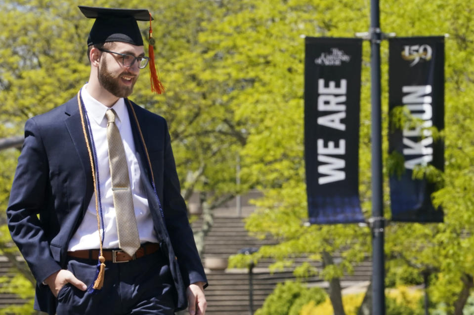 Recent University of Akron graduate Matthew Yokosuk poses for photo on campus, Thursday, May 13, 2021, in Akron, Ohio. Ohio Gov. Mike DeWine recently announced a weekly $1 million prize and full-ride college scholarships to entice more Ohioans to get the COVID-19 vaccine. (AP Photo/Tony Dejak)