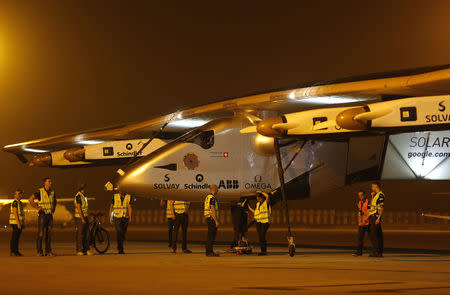 "Ground staff prepare to push the ""Solar Impulse 2"", a solar powered plane, into a hangar after it landed at the airport in Ahmedabad March 11, 2015. REUTERS/Amit Dave"
