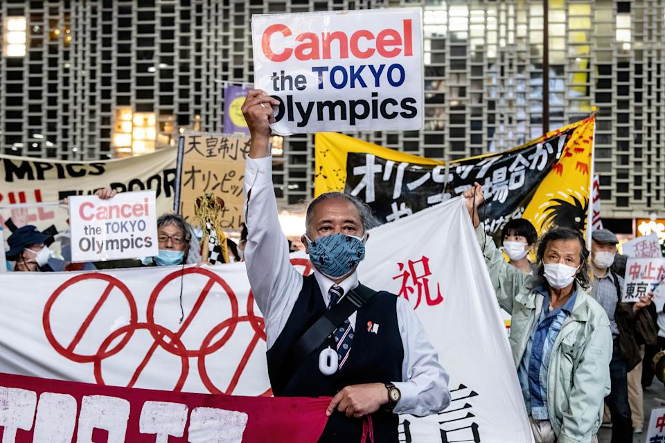 A protester holds a placard that says 'Cancel the Tokyo Olympics' during the demonstration.Demonstrators protest against the Tokyo Olympics with billboards and banners shouting 'Just stop it' marching through the Shimbashi and Ginza area. (Photo by Viola Kam/SOPA Images/LightRocket via Getty Images)