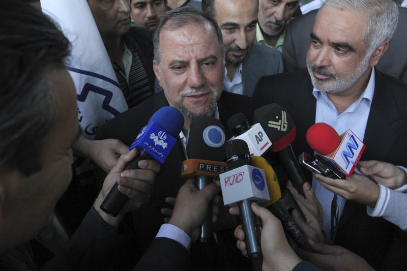 Iranian scientist, Mojtaba Atarodi, center, who was in U.S. custody since late 2011 over allegations he bought high-tech equipment in violation of U.S. sanctions on Iran, speaks to journalists, upon his arrival at the Imam Khomeini airport outside Tehran, Iran, Saturday, April 27, 2013. Atarodi arrived home via Oman, a Gulf state which has served as a mediator between Washington and Tehran before. (AP Photo/Vahid Salemi)