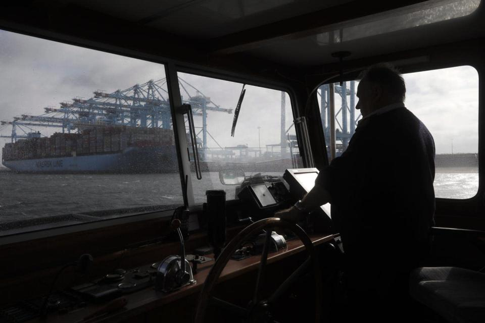 Looking at a large blue container ship through the window of a smaller boat