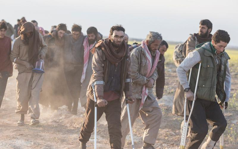 Men, likely fighters, who have fled from Isil's last remaining territory in Syria, in March 2019 - Sam Tarling for The Telegraph