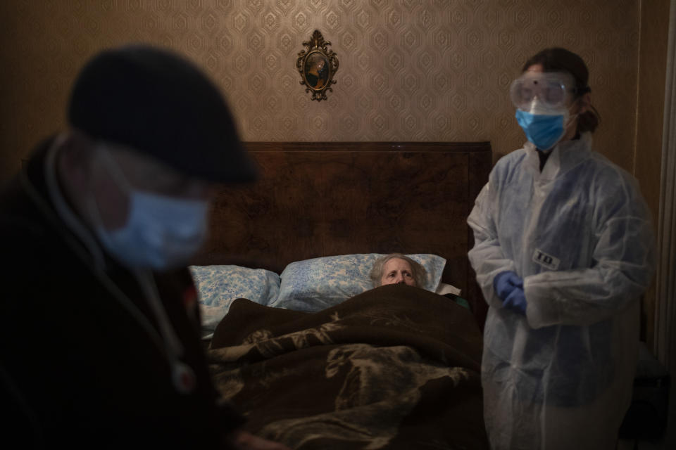 """Josefa Ribas, 86, who is bedridden, looks at nurse Alba Rodriguez as Ribas' husband, Jose Marcos, 89, stands by in their home in Barcelona, Spain, March 30, 2020, during the coronavirus outbreak. Ribas suffers from dementia, and Marcos fears for them both if the virus enters their home. """"If I get the virus, who will take care of my wife?"""" (AP Photo/Emilio Morenatti)"""