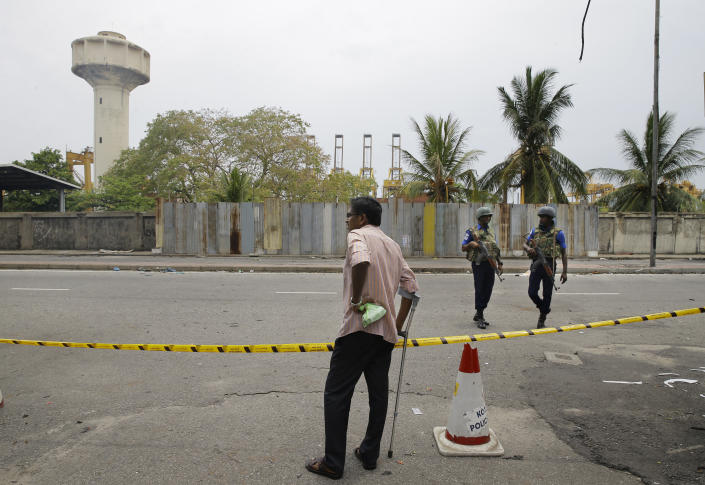 """A Sri Lankan man looks at a blocked road leading to St. Anthony's Church as Naval soldiers patrol, in Colombo, Sri Lanka, Monday, April 29, 2019. The Catholic Church in Sri Lanka says the government should crack down on Islamic extremists with more vigor """"as if on war footing"""" in the aftermath of the Easter bombings. (AP Photo/Eranga Jayawardena)"""