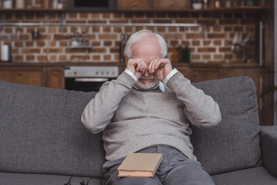 older man rubbing his eyes on the couch