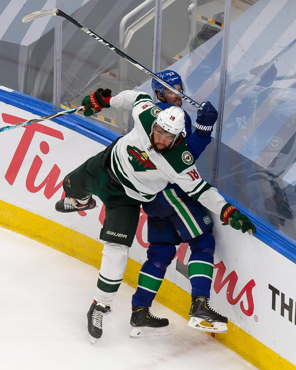 Minnesota Wild's Jordan Greenway (18) hits Vancouver Canucks' Alexander Edler (23) during the third period of an NHL hockey playoff game in Edmonton, Alberta, Tuesday, Aug. 4, 2020. (Codie McLachlan/The Canadian Press via AP)