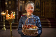Marija Balciul, a 10 -year-old, poses with Easter eggs after a cake and Easter egg blessing ceremony at the Prechistensky, the Cathedral Palace in Vilnius, Lithuania, Saturday, May 1, 2021. Orthodox Christians around the world celebrate Easter on Sunday, May 2. (AP Photo/Mindaugas Kulbis)