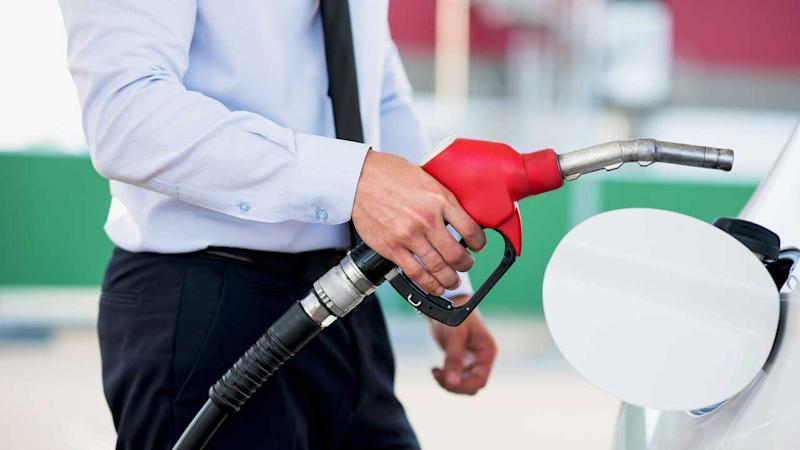 Man at petrol station about to fill car tank