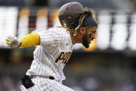 San Diego Padres' Fernando Tatis Jr. lunges as he reaches first base safely during the third inning of the team's baseball game against the Pittsburgh Pirates, Wednesday, May 5, 2021, in San Diego. (AP Photo/Gregory Bull)