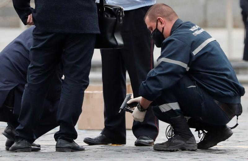 An investigator holds a gun in Red Square after an opposition activist reportedly simulated shooting himself in the head in a political protest, in Moscow