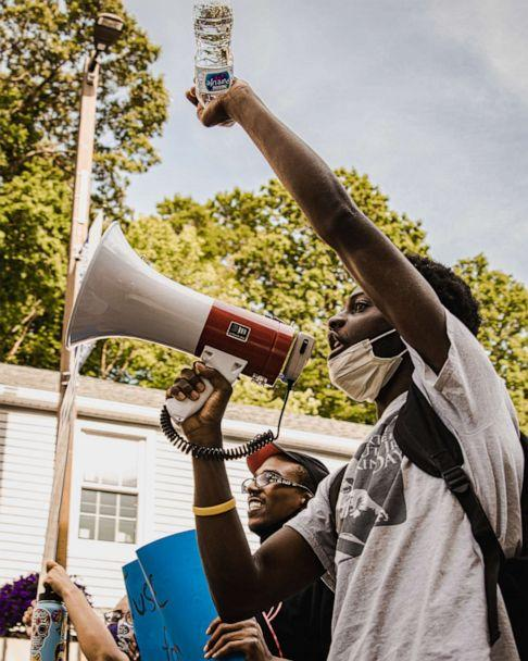 PHOTO: Junior Dufort raises his fist and yells through the microphone while marching through Norwich, Connecticut. (Courtesy Cam Curland)