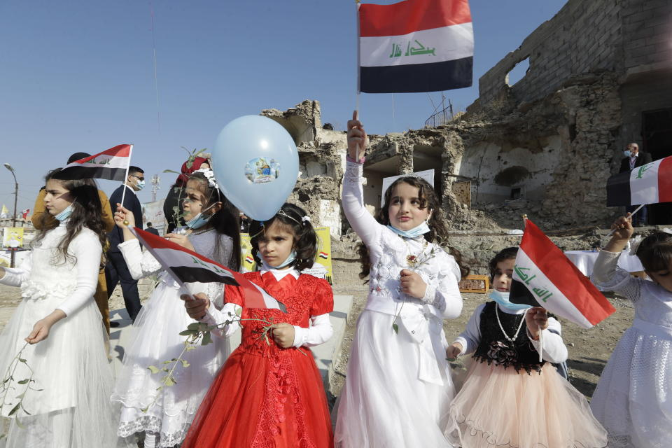 Children in their festive garment wave Iraqi flags to the camera as they arrive to join Pope Francis who will pray for the victims of war at Hosh al-Bieaa Church Square, in Mosul, Iraq, once the de-facto capital of IS, Sunday, March 7, 2021. The long 2014-2017 war to drive IS out left ransacked homes and charred or pulverized buildings around the north of Iraq, all sites Francis visited on Sunday. (AP Photo/Andrew Medichini)