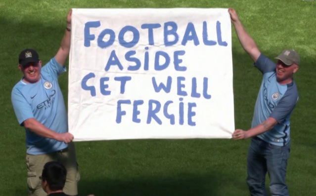 Manchester City fans held up a batter to support Sir Alex Ferguson in the wake of the legendary Manchester United manager's emergency surgery on Saturday. (Screenshot: NBC Sports Network)