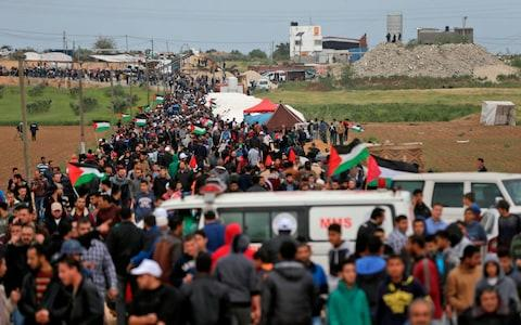 Palestinians marching past the tent city erected to commermoate Land Day, when six Arab Israelis were killed during 1976 demonstrations against Israeli confiscations of Arab land - Credit: MAHMUD HAMS/AFP