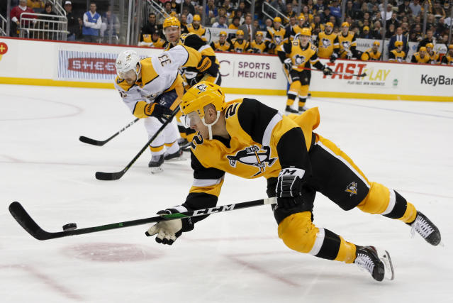 Pittsburgh Penguins' Chad Ruhwedel (2) dives to control the puck in front of Nashville Predators' Viktor Arvidsson (33) during the second period of an NHL hockey game Saturday, Dec. 28, 2019, in Pittsburgh. (AP Photo/Keith Srakocic)