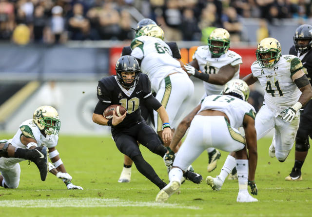 "UCF quarterback <a class=""link rapid-noclick-resp"" href=""/ncaaf/players/270182/"" data-ylk=""slk:Mckenzie Milton"">Mckenzie Milton</a> (10) runs the ball, looking to evade South Florida safety Tajee Fullwood (13) at Spectrum Stadium in Orlando, Fla., on Friday, Nov. 24, 2017. (Jacob Langston/Orlando Sentinel/TNS)"