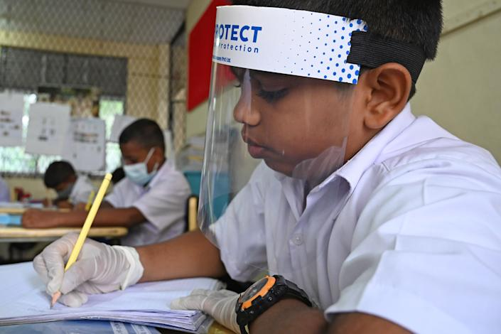 A student wearing a face shield attends school in Sri Lanka after their school was reopened this week. (Photo: LAKRUWAN WANNIARACHCHI via Getty Images)