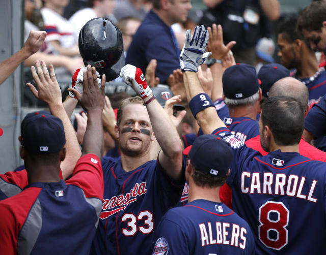 Minnesota Twins' Justin Morneau (33) celebrates in the dugout his grand slam scoring Joe Mauer, Pedro Florimon and Clete Thomas off Chicago White Sox relief pitcher Nate Jones during the seventh inning of a baseball game on Friday, Aug. 9, 2013, in Chicago. (AP Photo/Charles Rex Arbogast)