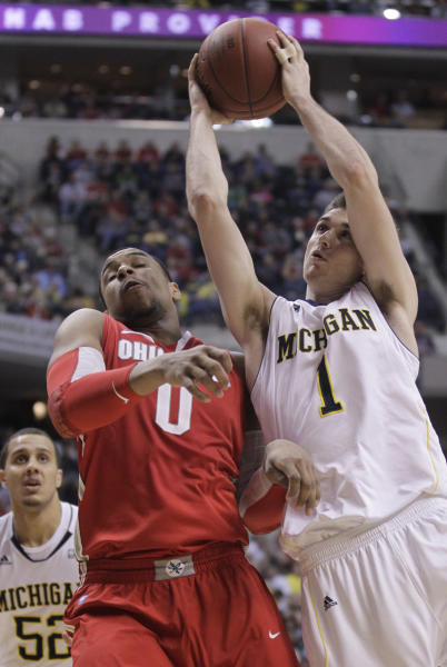 Michigan guard Stu Douglass (1) takes a shot against Ohio State forward Jared Sullinger (0) in the first half of an NCAA college basketball game in the semifinals of the Big Ten Conference tournament in Indianapolis, Saturday, March 10, 2012. At left is Michigan forward Jordan Morgan. (AP Photo/Michael Conroy)