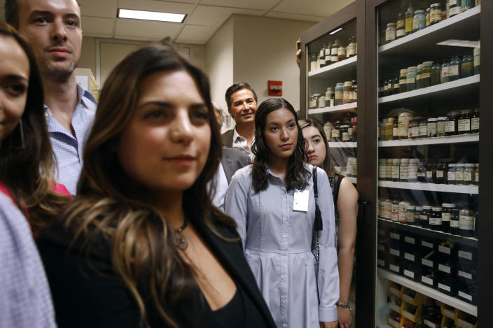 In this June 27, 2019 photo, family members of former U.S. Secret Service chief chemist Antonio Cantu tour an International Ink Library that was named in remembrance of Cantu at the Secret Service headquarters building in Washington. The library contains more than 15,000 samples of pen, marker and printer inks dating back to the 1920s. (AP Photo/Patrick Semansky)