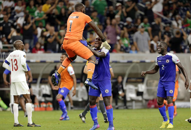 Haiti goalkeeper Jhony Placide (1) jumps onto defender Andrew Jean Baptiste (16) as Canada midfielder Atiba Hutchinson (13) and defender Carlens Arcus (2) watchg after Haiti's 3-2 win over Canada in a CONCACAF Gold Cup soccer quarterfinal Saturday, June 29, 2019, in Houston. (AP Photo/Michael Wyke)