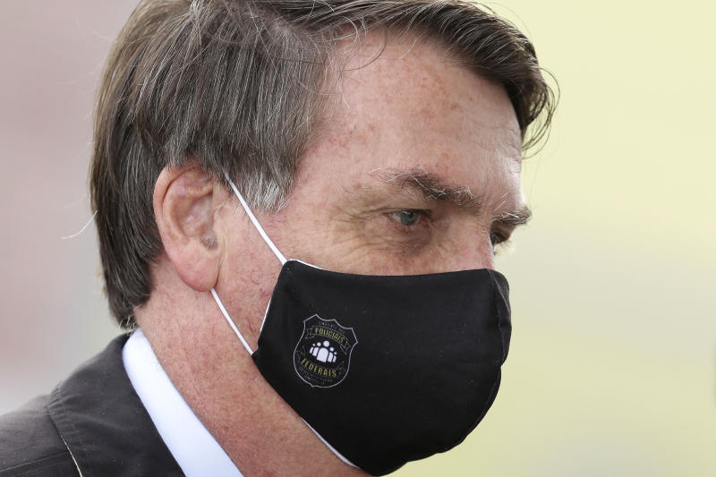 Brazil's President Jair Bolsonaro, wearing a face mask amid the new coronavirus, departs his official residence of Alvorada palace in Brasilia, Brazil, Monday, May 25, 2020. (AP Photo/Eraldo Peres)