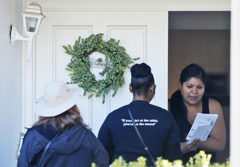 A resident takes voter registration paperwork from Democratic Party Precinct Chairs Angela Orr Heath, center, and Myla Senn, left, during for a voter registration drive in Garland, Texas, on Jan. 18, 2020. (LM Otero / AP)