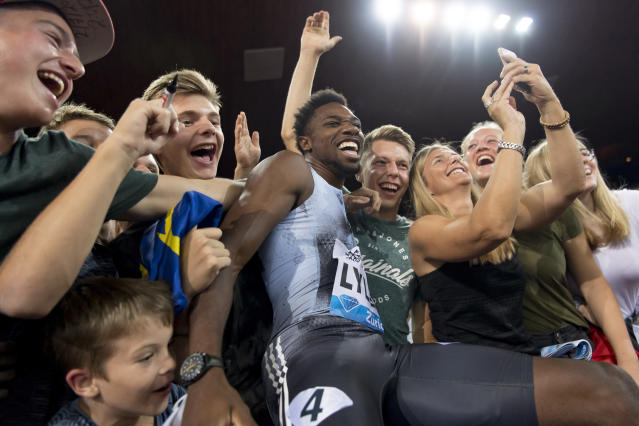 FILE - In this Aug. 29, 2019, file photo, Noah Lyles, of the United States, celebrates with fans after winning the men's 100m race during the Weltklasse IAAF Diamond League international athletics meet in Zurich, Switzerland. The most promising signal that track and field remains in good hands even after Usain Bolt's retirement comes from a 22-year-old American named Noah Lyles who appreciates the Jamaican superstar more for what he did after his races than during them. When Lyles spends time studying Bolt on video, he looks not at the lanky speedster's form in between the lines, but at the dancing, rollicking post-race celebrations Bolt concocted to make his sport can't-miss viewing whenever he was on the track.(Jean-Christophe Bott/Keystone via AP, File)