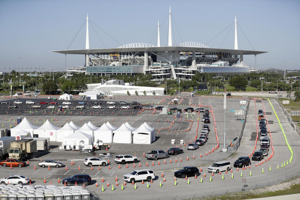 FILE - In this March 30, 2020, file photo, cars line up at a drive-thru coronavirus testing site in front of Hard Rock Stadium in Miami Gardens, Fla. Nobody can say with precise certainty how many coronavirus tests that the NBA, NHL and Major League Baseball would need before those leagues can resume playing games. (AP Photo/Wilfredo Lee, File)