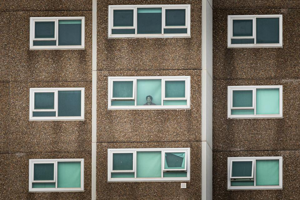 A lone woman looking out the window of her apartment at the North Melbourne Public housing flats.