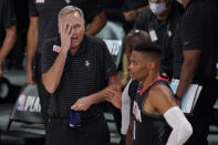 Houston Rockets head coach Mike D'Antoni, left, puts a hand to his face as he speaks with an official standing behind Russell Westbrook, right front, during the second half of an NBA first-round playoff basketball game against the Oklahoma City Thunder in Lake Buena Vista, Fla., Wednesday, Sept. 2, 2020. (AP Photo/Mark J. Terrill)