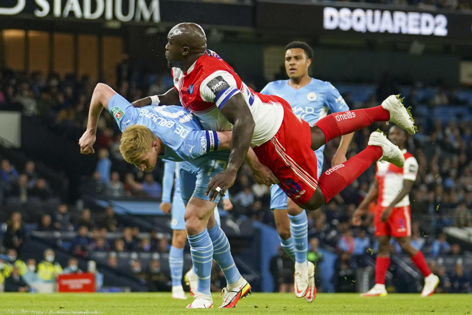 Manchester City's Kevin De Bruyne, left, and Wycombe Wanderers Adebayo Akinfenwa collide as they compete for the ball during the English League Cup third round soccer match between Manchester City and Wycombe Wanderers at Etihad Stadium, in Manchester England, Tuesday, Sept. 21, 2021. (AP Photo/Dave Thompson)