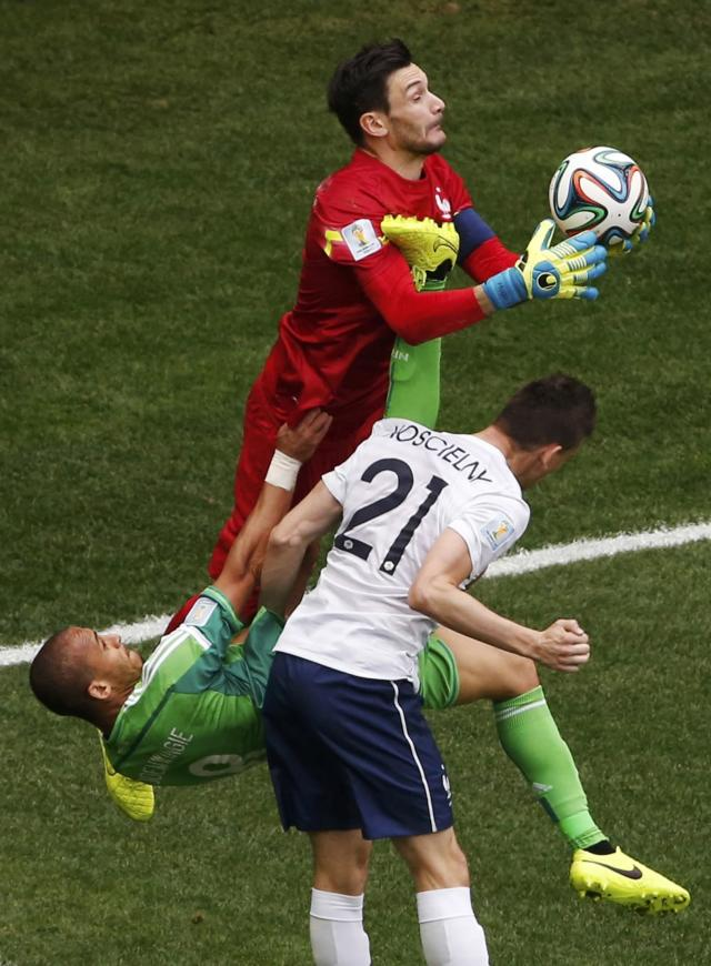 France's goalkeeper Hugo Lloris (top) makes a save near teammate Laurent Koscielny (21) and Nigeria's Peter Odemwingie during their 2014 World Cup round of 16 game at the Brasilia national stadium in Brasilia June 30, 2014. REUTERS/David Gray (BRAZIL - Tags: SOCCER SPORT WORLD CUP TPX IMAGES OF THE DAY)