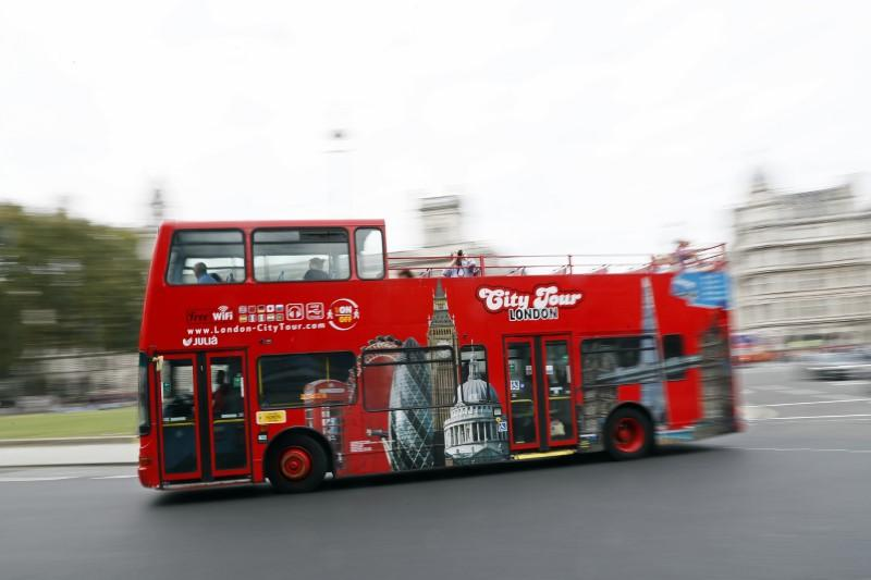 A sightseeing bus drives past Parliament Square in London