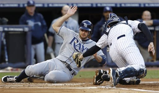Tampa Bay Rays' Jeff Keppinger, left, is tagged out at the plate by New York Yankees catcher Chris Stewart on Carlos Pena's first-inning RBI-single during their baseball game at Yankee Stadium in New York, Thursday, May 10, 2012. (AP Photo/Kathy Willens)