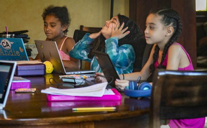 "Rosie Roth, center, takes a breather from typing class seated between Andie Bristow, left, and Allison Furbush at the Bristows' dining room table. <span class=""copyright"">(Gina Ferazzi / Los Angeles Times)</span>"